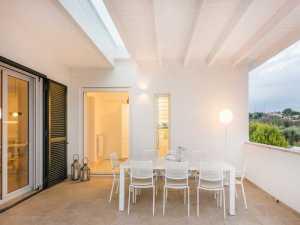 Ampliamento cucina con portico in legno biancorealizzato mediante la fornitura e posa in opera di travi e pilastri in legno lamellare d'abete.
