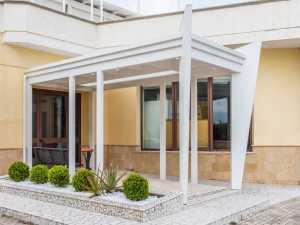 Copertura per ingressoin legno bianco e vetro.